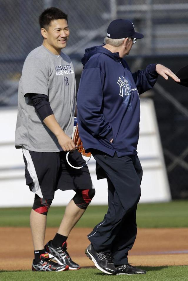 New York Yankees pitcher Masahiro Tanaka, left, of Japan, smiles as he talks to pitching coach Larry Rothschild during practice at the Yankees' minor league facility Thursday, Feb. 13, 2014, in Tampa, Fla. (AP Photo/Chris O'Meara)