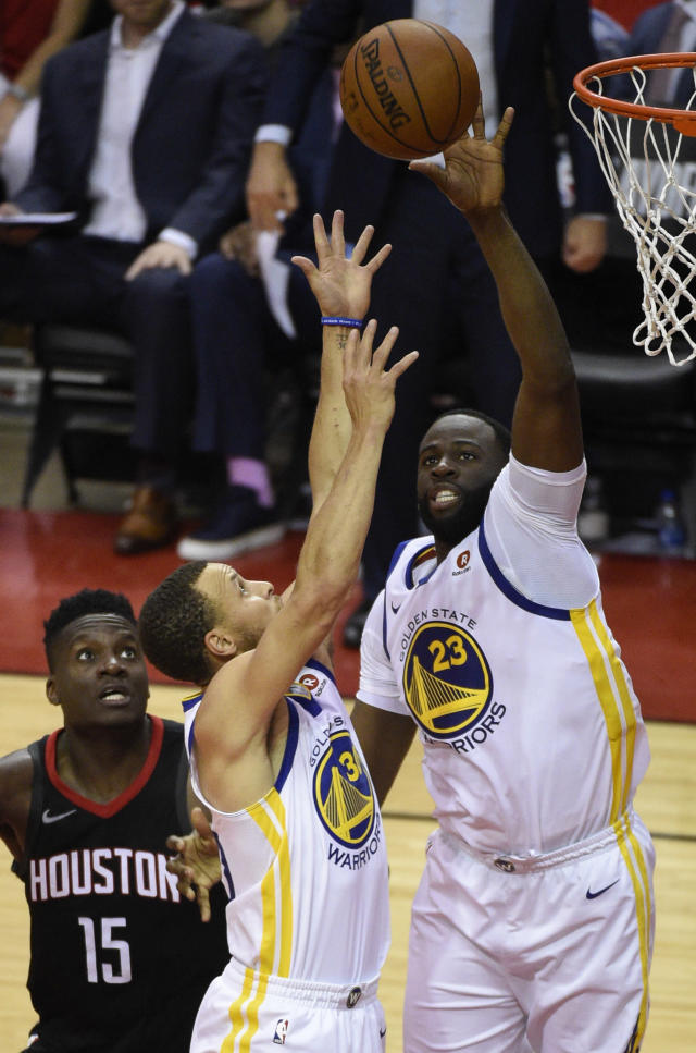 Golden State Warriors forward Draymond Green (23) and guard Stephen Curry vie for a rebound as Houston Rockets center Clint Capela (15) watches during the second half of Game 2 of the NBA basketball playoffs Western Conference finals Wednesday, May 16, 2018, in Houston. (AP Photo/Eric Christian Smith)