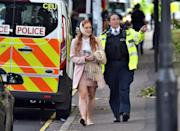 <p>An unidentified, injured female Tube passenger is escorted from the scene of the blast by police on Friday morning. (PA) </p>