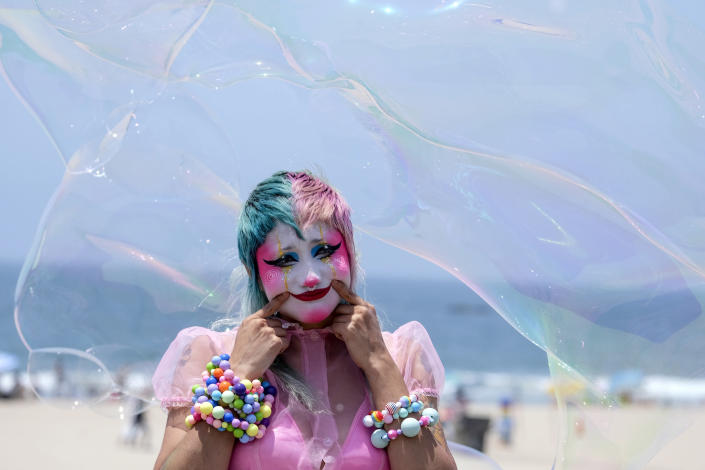 Stephanie Berry, a makeup artist, poses for a photo as bubbles fly over in the heat at Santa Monica Beach on Wednesday, June 16, 2021, in Santa Monica, Calif. (AP Photo/Ringo H.W. Chiu)