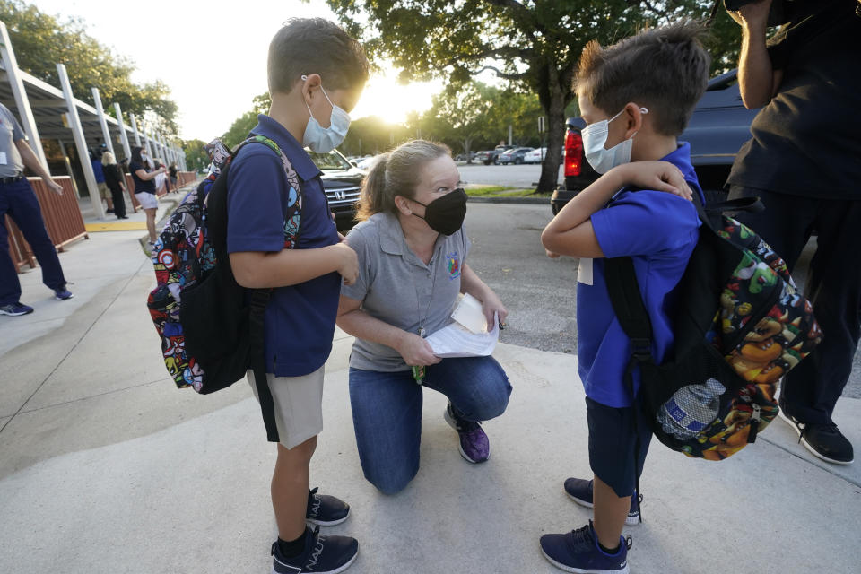 Juliana Orosi, center, checks in students Thomas, left, and Ethan Guillen on the first day of Broward County, Florida schools phased reopening for face-to-face eLearning at Fox Trail Elementary School, on Oct. 9, 2020, in Davie, Fla. (Wilfredo Lee/AP)