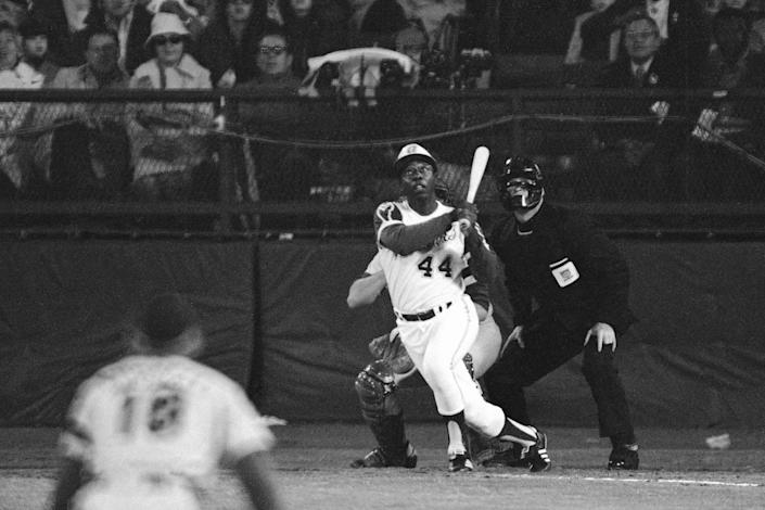 FILE - Atlanta Braves' Hank Aaron eyes the flight of the ball after hitting his 715th career homer in a game against the Los Angeles Dodgers in Atlanta, Ga., in this Monday night, April 8, 1974, file photo. Aaron broke Babe Ruth's record of 714 career home runs. Dodgers southpaw pitcher Al Downing, catcher Joe Ferguson and umpire David Davidson look on. (AP Photo/Harry Harrris)