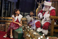Gracelynn Blumenfeld, 8, visits with Santa through a transparent barrier at a Bass Pro Shop in Bridgeport, Conn., Tuesday, Nov. 10, 2020. Malls are doing all they can to keep the jolly old man safe from the coronavirus, including banning kids from sitting on his knee, completely changing what a Santa visit looks like. (AP Photo/Seth Wenig)