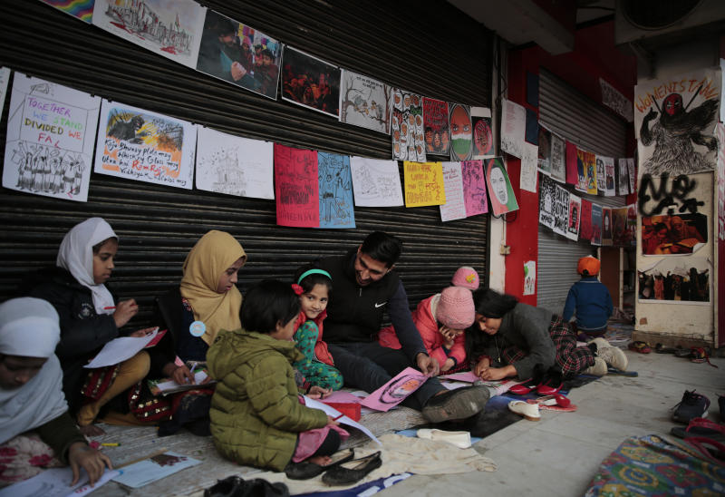 In this Tuesday, Jan. 21, 2020 photo, young girls draw sketches near the protest site in New Delhi's Shaheen Bagh area, India. Muslim women are transcending the confines of their homes to lay claim to the streets of this nondescript Muslim neighborhood in the Indian capital and slowly transforming it into a nerve center of resistance against a new citizenship law that has unleashed protests across the country. The women, sitting in the middle of a major highway, have taken turns maintaining an around the clock sit-in for more than a month. They sing songs of protest and chant anti-government slogans, some cradling babies, others laying down rugs to make space for more people to sit. (AP Photo/Altaf Qadri)