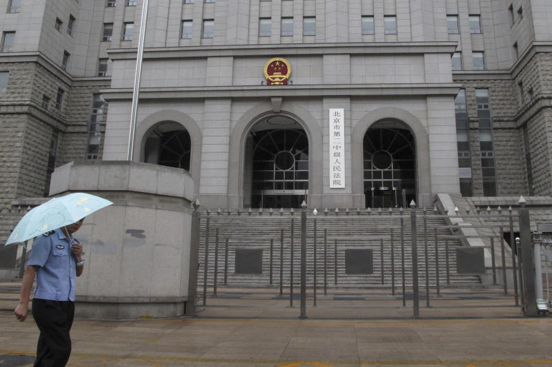 A policeman walks past the gate of Beijing No. 2 Intermediate People's Court while former railways minister Liu Zhijun stands trial inside, in Beijing, China, Sunday, June 9, 2013. Liu, the man who once ran China's powerful railways ministry and oversaw its high-profile bullet train development, sought leniency for corruption crimes at Sunday's opening of one of the country's biggest graft cases in years. (AP Photo/Gillian Wong)
