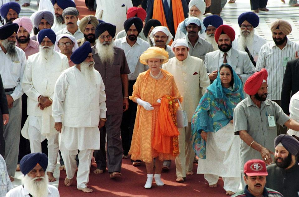 Queen Elizabeth removed her shoes to visit the Golden Temple Of Amritsar in Punjab, India. She later laid a wreath at the site where British soldiers killed nearly 400 unarmed protesters in 1919. (Photo: Tim Graham via Getty Images)