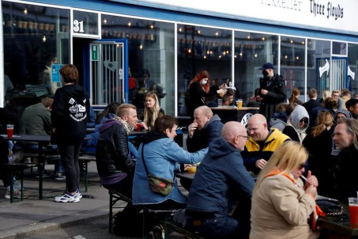 Customers sit outside a bar after COVID-19 lockdown partial lift, in Copenhagen