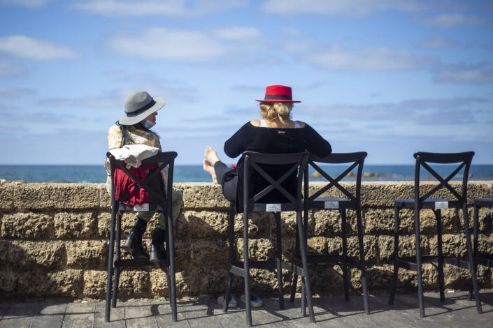 Women sit in a caffe-bar overlooking the Mediterranean Sea as restrictions are eased following months of government-imposed shutdowns, in Tel Aviv, Israel, Sunday, March 7, 2021. Israel reopened most of its economy Sunday as part of its final phase of lifting coronavirus lockdown restrictions, some of them in place since September. (AP Photo/Ariel Schalit)