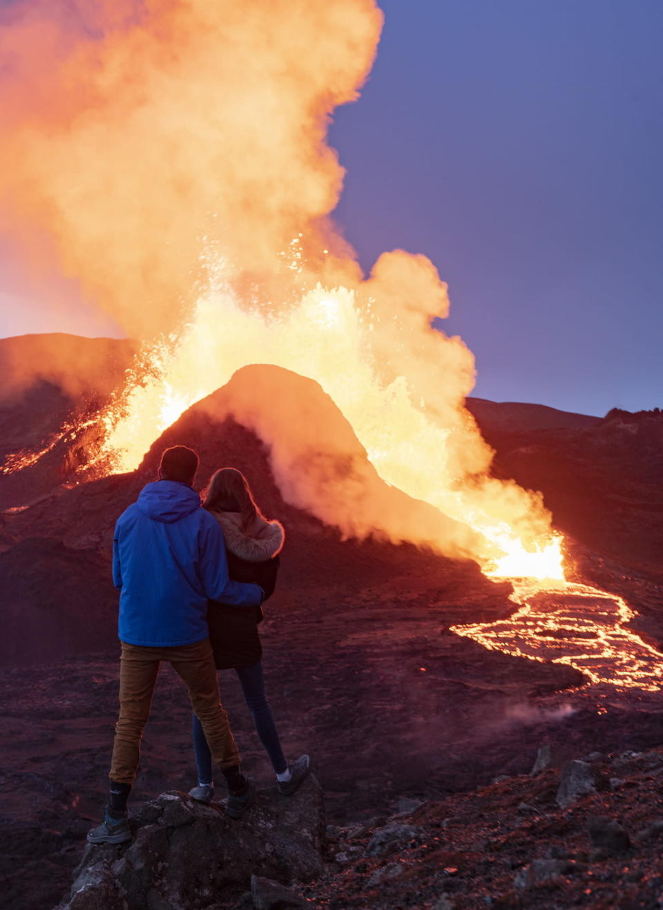 People watch as lava flows from an eruption of the Fagradalsfjall volcano on the Reykjanes Peninsula in southwestern Iceland on Thursday, May 13, 2021. (AP Photo/Miguel Morenatti)