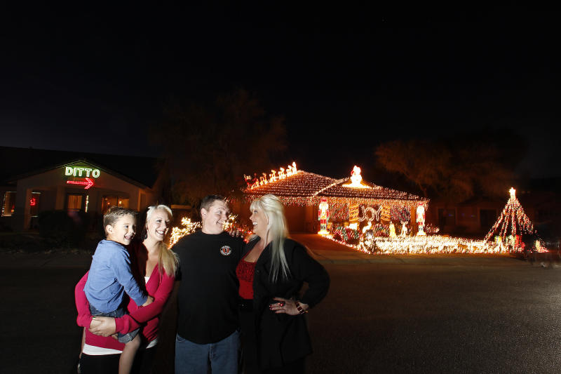 "Kristina Green, right, her daughter Breanah Gray, second left, and grandson Cameron Gray, left, laugh together with neighbor Eric Cyr as they pose in front of their homes, Tuesday Dec. 11, 2012, in Maricopa, Ariz. Green could not compete with Cyr's 20,000 Christmas lights on his home, so she has put up a 450 light display that says ""DITTO"" with an arrow pointing to Cyr's home. (AP Photo/Ross D. Franklin)"