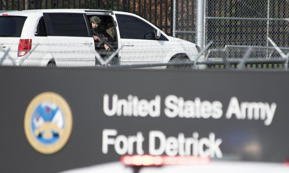 A member of the Frederick police department special response team peers out of a minivan before the team entered Fort Detrick in a convoy of vans and sedans after a shooting in Riverside Tech Park, near the Royal Farms on Monocacy Boulevard.