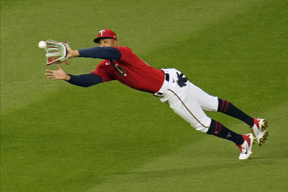 Minnesota Twins center fielder Byron Buxton makes a diving catch of a fly ball off the bat of Texas Rangers' David Dahl in the seventh inning of a baseball game, Tuesday, May 4, 2021, in Minneapolis. (AP Photo/Jim Mone)