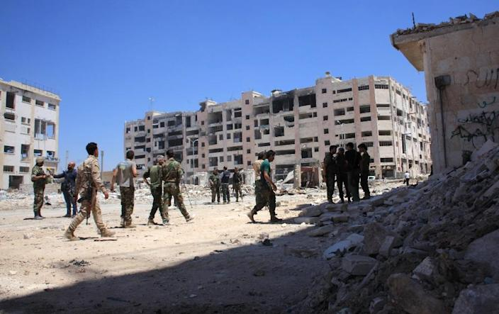 Syrian army soldiers patrol the area around the entrance of Bani Zeid after seizing the district of Leramun, on the northwest outskirts of Aleppo, from rebels on July 28, 2016 (AFP Photo/George Ourfalian)