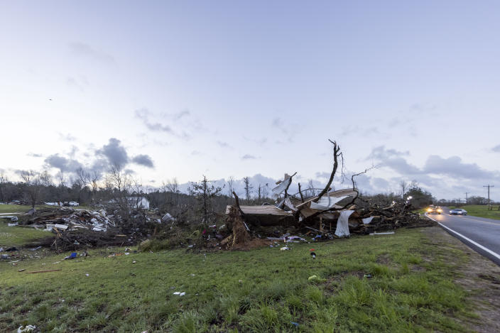 The sun rises over weather-damaged properties at the intersection of County Road 24 and 37 in Clanton, Ala., the morning following a large outbreak of severe storms across the southeast, Thursday, March 18, 2021. (AP Photo/Vasha Hunt)
