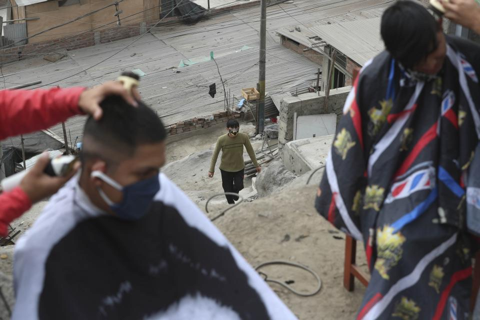 A resident watches as his neighbors receive free haircuts from Josue Yacahuanca, 21-year-old barber, and his brother Luis, in the San Juan de Lurigancho neighborhood of Lima, Peru, Friday, June 19, 2020. Like thousands of businesses across Peru, Yacahuanca's barbershop _ called D Barrio Shop _ closed its doors March 16 under quarantine orders. Since then, he's watched his personal finances be pulverizing. But, he's brushed it off, deciding to help others with the skills he has. (AP Photo/Martin Mejia)