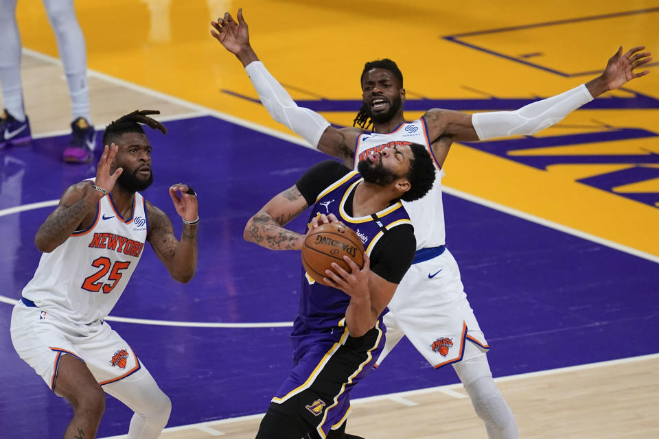 Los Angeles Lakers forward Anthony Davis, bottom right, reacts after getting hit in the face by New York Knicks center Nerlens Noel, top right, during the fourth quarter of an NBA basketball game Tuesday, May 11, 2021, in Los Angeles. New York Knicks forward Reggie Bullock (25) is at left. (AP Photo/Ashley Landis)