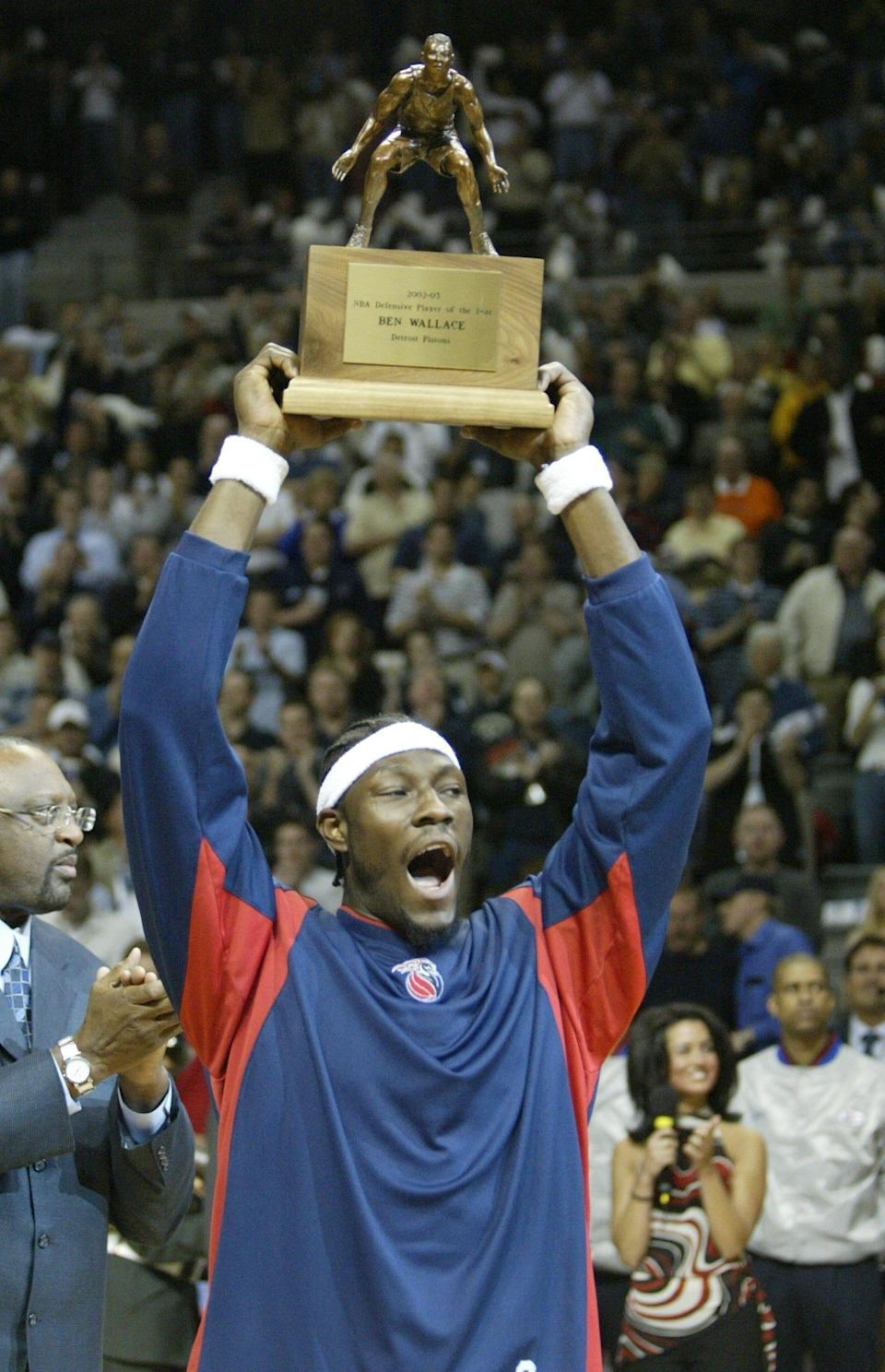 Pistons' Ben Wallace holds up his NBA Defensive Player of the Year trophy prior to Game 2 of the playoff series vs. the Orlando Magic at the Palace of Auburn Hills, April 23, 2003.
