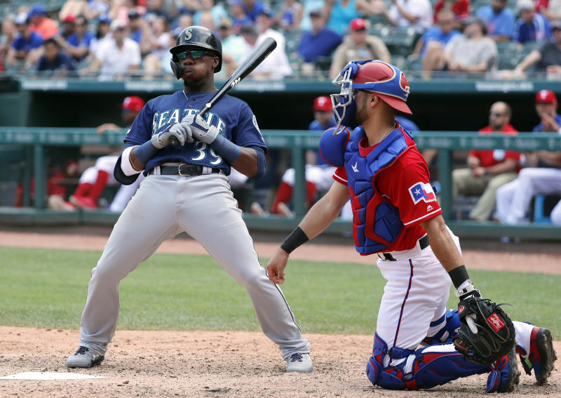 Seattle Mariners' Shed Long, leans back from the plate after a strike call as Texas Rangers catcher Isiah Kiner-Falefa, right, looks on in the ninth inning of a baseball game in Arlington, Texas, Wednesday, May 22, 2019. Long struck out in the at-bat in the 2-1 Rangers win. (AP Photo/Tony Gutierrez)