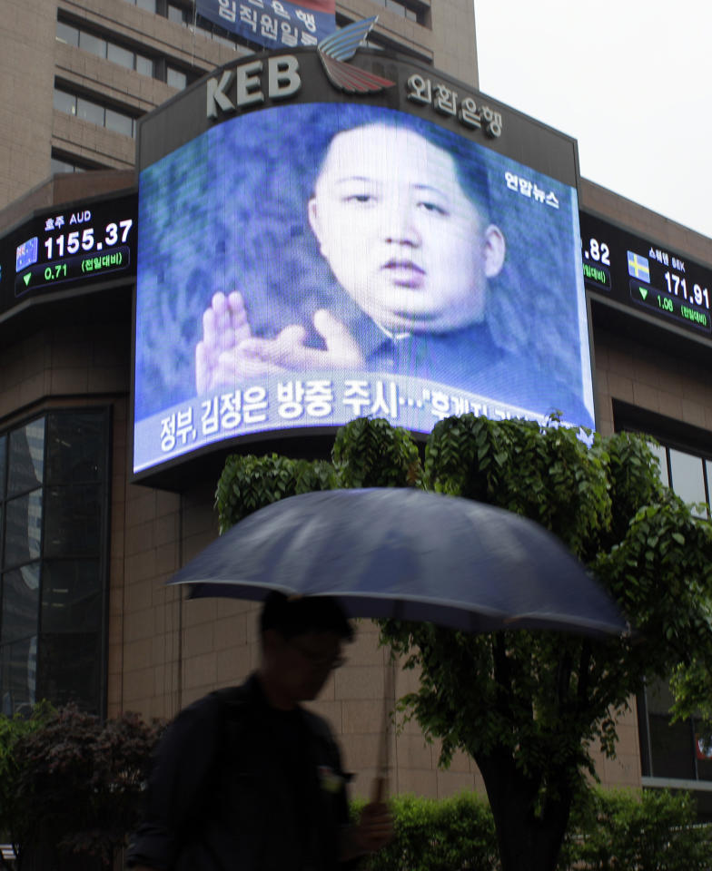 A man walks by a huge screen showing a file footage of Kim Jong Un, the youngest son of North Korean leader Kim Jong Il, in downtown Seoul, South Korea, Friday, May 20, 2011. The young son and heir apparent of North Korea's leader traveled Friday to neighboring China, news reports said, in a visit to his country's key ally and benefactor that would mark his biggest-yet diplomatic responsibility.