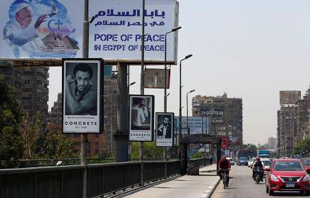 Vehicles drive past a billboard ahead of Pope Francis' visit in Cairo, Egypt April 26, 2017. REUTERS/Amr Abdallah Dalsh