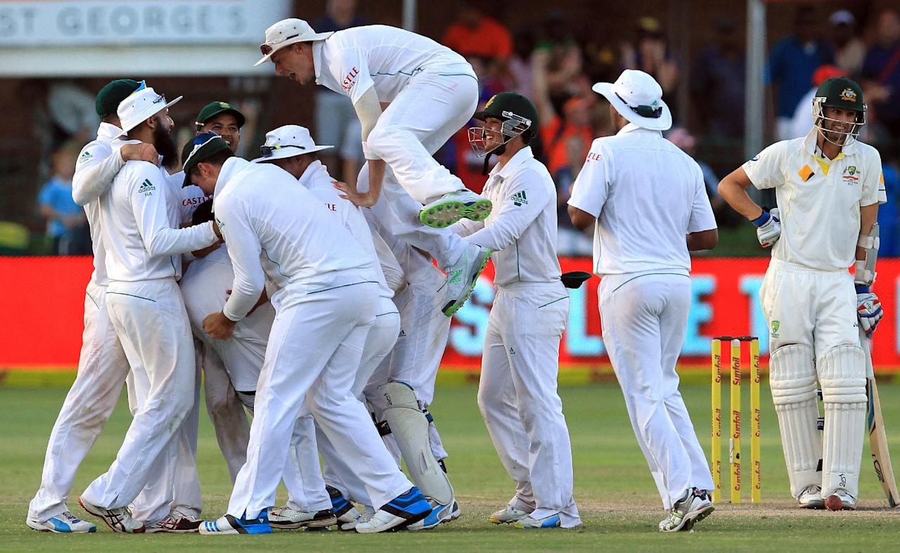 South Africa's players celebrate the winning wicket as Australia's batsman Nathan Lyon, right, watches on the fourth day of their 2nd cricket test match at St George's Park in Port Elizabeth, South Africa, Sunday, Feb. 23, 2014. South Africa beat Australia by 231 runs. (AP Photo/ Themba Hadebe)