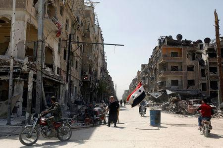 A Syrian flag flutters along a damaged street at the city of Douma in Damascus