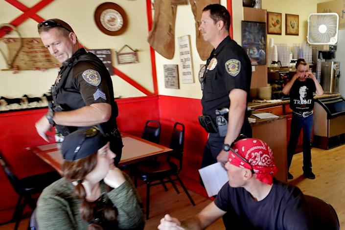 "Police officers in Wickenburg, Ariz., leave the Horseshoe Cafe on May 1 after informing owner Debbie Thompson, standing at right, that she was in violation of the state's stay-at-home order. <span class=""copyright"">(Matt York / Associated Press)</span>"