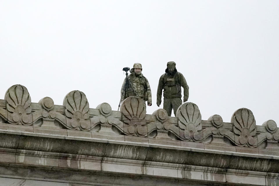 Law enforcement officers stand atop the Capitol in anticipation of protests Monday, Jan. 11, 2021, at the Capitol in Olympia, Wash. According to organizers, some protesters are unhappy the Legislature will be meeting virtually and in sessions not open to the public, due to the COVID-19 pandemic, during the 2021 session which opens Monday. Washington Gov. Jay Inslee activated members of the National Guard this week to work with the Washington State Patrol to protect the Capitol campus. (AP Photo/Ted S. Warren)