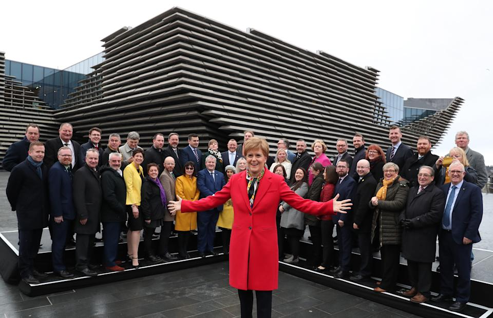 First Minister Nicola Sturgeon joins SNP's newly elected MPs for a group photo call outside the V&A Museum in Dundee. PA Photo. Picture date: Saturday December 14, 2019. See PA story POLITICS Election Scotland. Photo credit should read: Andrew Milligan/PA Wire (Photo by Andrew Milligan/PA Images via Getty Images)