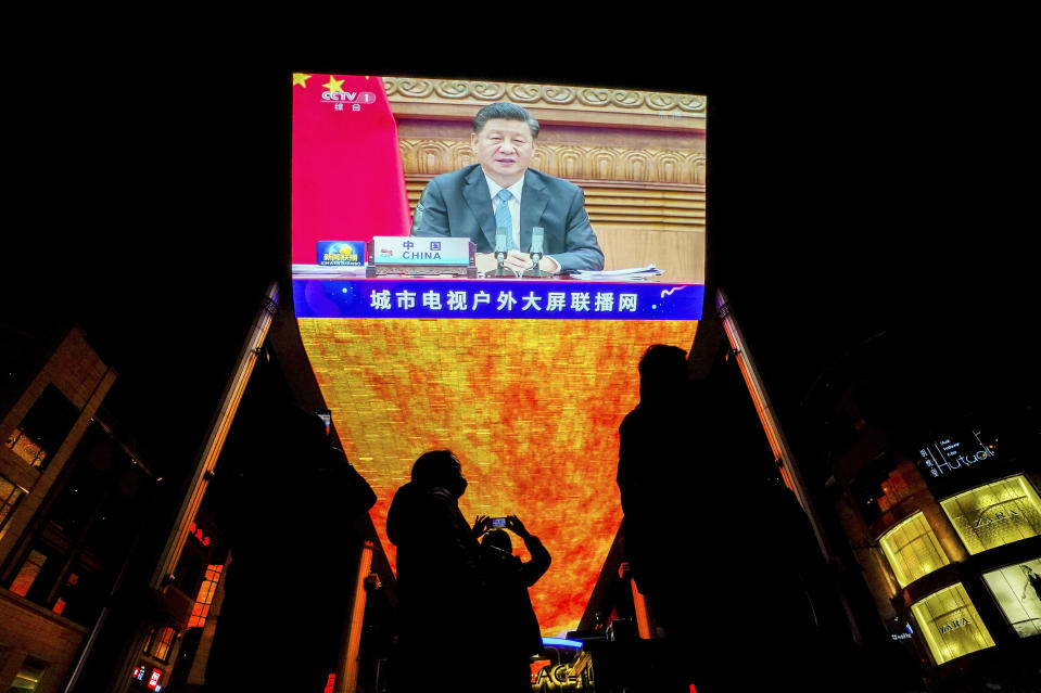People wearing face masks to help curb the spread of the coronavirus gather near a giant TV screen broadcasting a news of Chinese President Xi Jinping speaks as he participates in a virtual G20 summit, at a shopping mall in Beijing, Sunday, Nov. 22, 2020. The Group of 20 summit opened on Saturday with appeals by the world's most powerful leaders to collectively chart a way forward as the coronavirus pandemic overshadows this year's gathering, transforming it from in-person meetings to a virtual gathering of speeches and declarations. (AP Photo/Andy Wong)