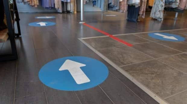 Arrows directing customers around the store space are one of the protective measures at Boutique Moi in Gatineau, Que., May 16, 2021, the day before it was allowed to reopen for in-person shopping under relaxed provincial rules.