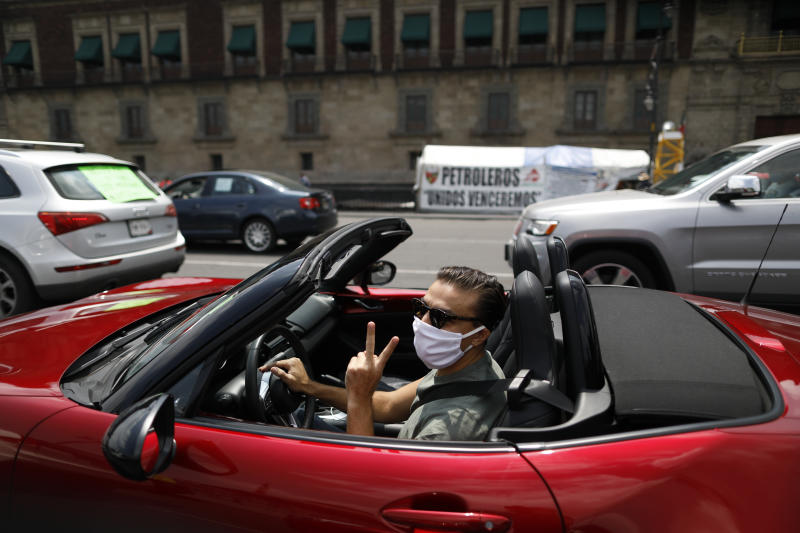A driver participates in a caravan of cars protest calling for Mexican President Andres Manuel Lopez Obrador to step down, in front of the National Palace in Mexico City, Saturday, May 30, 2020. Hundreds of cars, many adorned with flags and signs criticizing Lopez Obrador, drove in circles past the National Palace on Saturday, honking their horns to protest against the president and his handling of the new coronavirus pandemic. (AP Photo/Rebecca Blackwell)
