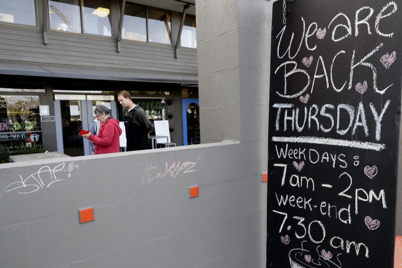 Customers enter their details before entering a cafe in Christchurch, New Zealand, Thursday, May 14, 2020. New Zealand lifted most of its remaining lockdown restrictions from midnight Wednesday as the country prepares for a new normal. Malls, retail stores and restaurants are all reopening Thursday in the South Pacific nation of 5 million, and many people are returning to their workplaces. (AP Photo/Mark Baker)