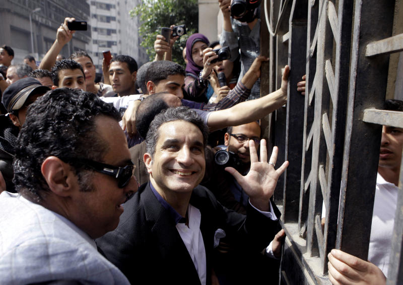 """FILE - In this Sunday, March 31, 2013 file photo, Egyptian popular television satirist Bassem Youssef, who has come to be known as Egypt's Jon Stewart, waves to is supporters as he enters Egypt's state prosecutors office to face accusations of insulting Islam and the country's Islamist leader in Cairo, Egypt. After more than four months away, the man known as """"Egypt's Jon Stewart"""" returns the airwaves Friday in a country radically different from the one he previously mocked. Satirist Bassem Youssef's weekly """"El-Bernameg,"""" or """"The Program"""" in Arabic, mocked the country's first elected Islamist president and his supporters for mixing religion and politics, took them to task for failing to be inclusive or deliver on people's demands for change_ to the extent that some said he was one of the main reasons people turned against Mohammed Morsi. (AP Photo/Amr Nabil, File)"""
