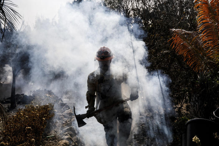 <p>L.A. County firefighter Battalion 13 Captain Victor Correa helps put out hotspot in a neighborhood razed by the Woolsey fire on Harvester road on Monday in Malibu, Calif. (Photo: Marcus Yam/Los Angeles Times via Getty Images) </p>