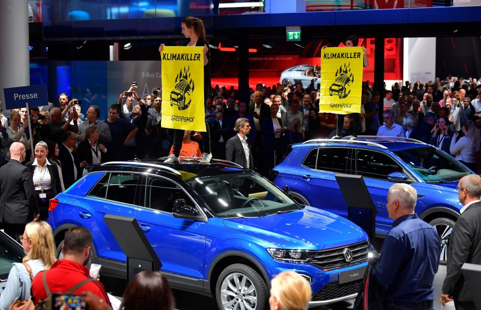 """Greenpeace activists standing on Volkswagen (VW) cars hold posters reading """"Climate Killers"""" as they demonstrate at the booth of Volkswagen, where German Chancellor Angela Merkel touring the fair grounds was expected after officially opening the International Auto Show (IAA) in Frankfurt am Main, western Germany, on September 12, 2019. - Climate protection protesters say the car sector is failing to reduce carbon emissions despite a massive push for new electric vehicles. (Photo by Tobias SCHWARZ / AFP)        (Photo credit should read TOBIAS SCHWARZ/AFP/Getty Images)"""
