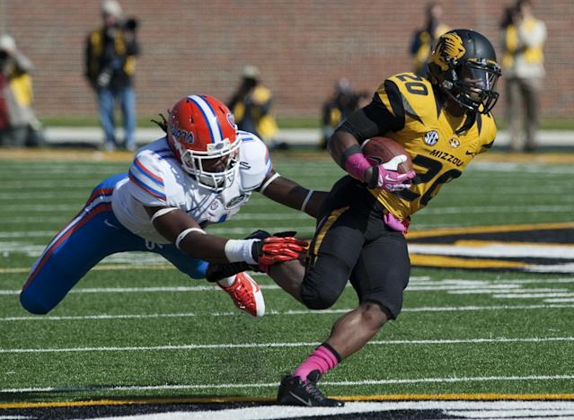 Missouri running back Henry Josey, right, runs past the grasp of Florida's Neiron Ball, left, during the first quarter of an NCAA college football game Saturday, Oct. 19, 2013, in Columbia, Mo. (AP Photo/L.G. Patterson)