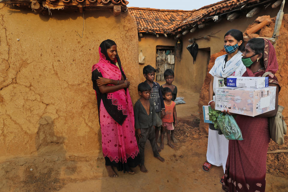 A health worker, right, persuades village woman Maju Kol, left, to get vaccinated against the coronavirus at Jamsoti village, Uttar Pradesh state, India, on June 8, 2021. India's vaccination efforts are being undermined by widespread hesitancy and fear of the jabs, fueled by misinformation and mistrust. That's especially true in rural India, where two-thirds of the country's nearly 1.4 billion people live. (AP Photo/Rajesh Kumar Singh)