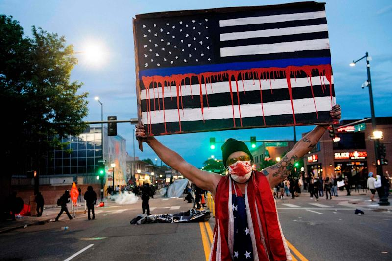 A demonstrator holds up a sign during a protest in Denver, Colorado, on May 31, 2020, over the death of George Floyd: AFP via Getty Images