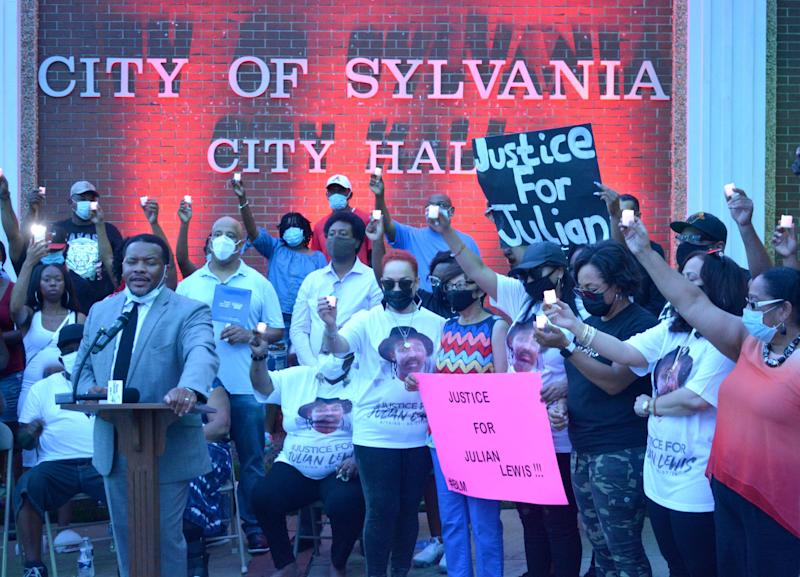 Francys Johnson, a Statesboro civil rights attorney, addresses a crowd of 200 in downtown Sylvania, Georgia on Aug. 14, as members of the Julian Edward Roosevelt Lewis family hoist lit candles in honor of Lewis.