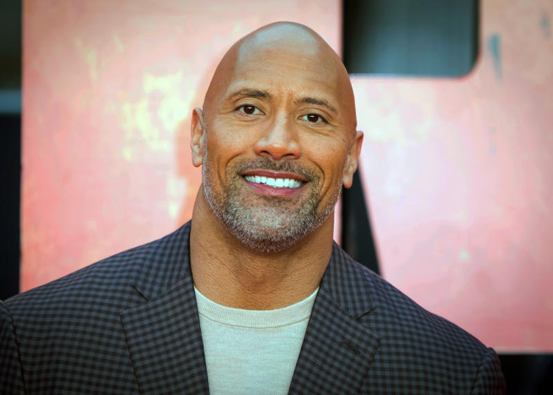 """FILE - In this April 11, 2018, file photo, actor Dwayne Johnson poses for photographers at the premiere of the """"Rampage,"""" in London. Johnson will host and Justin Bieber, Miley Cyrus and Jennifer Hudson will perform on a globally broadcast concert calling on world leaders to make coronavirus tests and treatment available and equitable for all. The advocacy organization Global Citizen and the European Commission announced Monday, June 22, 2020 that Global Goal: Unite for Our Future — The Concert will air on June 27. (Photo by Vianney Le Caer/Invision/AP, File)"""