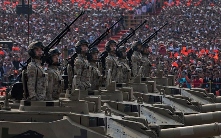 Chinese soldiers ride atop tanks as they drive in a parade - Getty