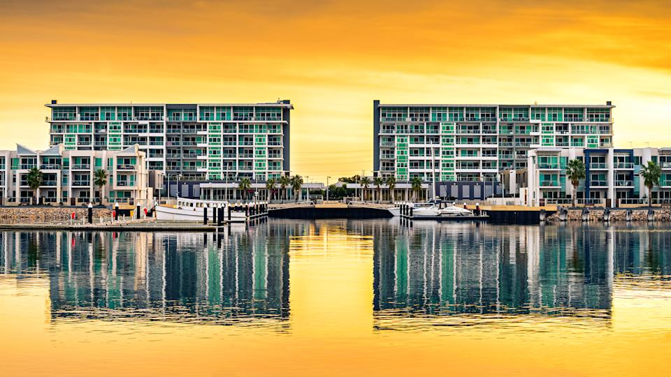 Wirra Drive apartment buildings reflecting in the river at New Port at sunset, Port Adelaide, South Australia