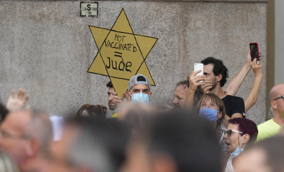 """FILE - In this Saturday, July 24, 2021 file photo, people stage a protest against the """"green pass"""" in Milan, Italy. Protesters in Italy and in France have been wearing yellow Stars of David, like the ones Nazis required Jews to wear to identify themselves during the Holocaust. Some carry signs likening vaccine passes to dictatorships. (AP Photo/Antonio Calanni, File)"""