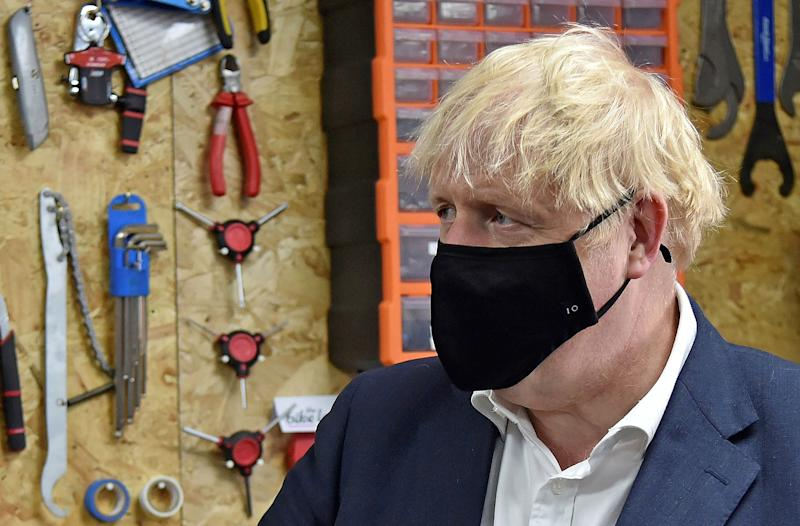 Britain's Prime Minister Boris Johnson wearing a black face mask featuring a number '10', due to the COVID-19 pandemic, talks to the owner of the the Cycle Lounge, Rodney Rouse, a bicycle repair shop in Beeston, central England, on July 28, 2020, during an event to launch the the government's new cycling intuitive to help get people fitter. - The British government promised Monday to build thousands of miles of new bike lanes to get people moving and healthy after months of coronavirus lockdown. Prime Minister Boris Johnson's pledge comes on the heels of a plan to force restaurants to display calories on menus as part of a broader effort to win the battle of the bulge. (Photo by Rui Vieira / POOL / AFP) (Photo by RUI VIEIRA/POOL/AFP via Getty Images)