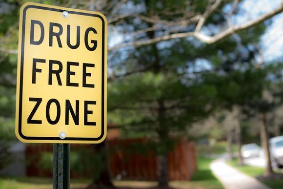 A drug-free zone street sign in a quiet neighborhood.