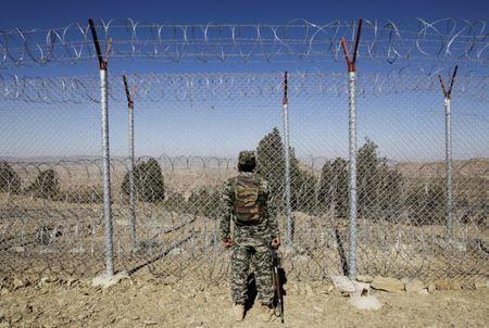 A soldier stands guard along the border fence at the Angoor Adda outpost on the border with Afghanistan in South Waziristan, Pakistan October 18, 2017.  REUTERS/Caren Firouz