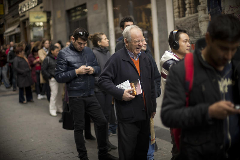 """A man yawns as he queue in long lines to buy tickets for the cash-strapped country's famed Christmas lottery, in Madrid, Friday, Dec. 21, 2012. Many players say they're hoping to win so they can pay off debt or help relatives facing heavy economic burdens. Known as """"El Gordo"""" (The Fat One) and billed as the world's richest lottery, the drawing will hand out about 2.5 billion euro ($3.3 billion) on Saturday. The top prize is about 400,000 euro ($530,000) but there are expected to be hundreds or thousands of tickets awarded for that amount. (AP Photo/Daniel Ochoa de Olza)"""