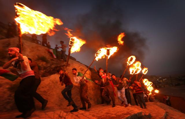<p>Iraqi Kurds wave Kurdish flags and hold torches as they walk up a mountain during a gathering to show support for the upcoming independence referendum and encourage people to vote in the town of Akra, some 300 miles north of Baghdad, Sept. 10, 2017. (Photo: Safin Hamed/AFP/Getty Images) </p>