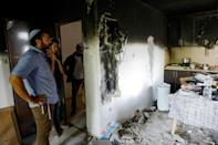 Israelis stand in a home that was damaged by fire during the intra-communal violence in Lod (AFP/GIL COHEN-MAGEN)